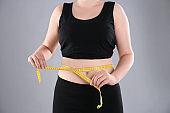 Overweight woman measuring waist before weight loss on color background