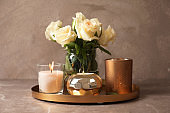 Tray with burning wax candles and flowers on table