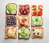 Tasty toast bread with fruits, berries and vegetables on light background