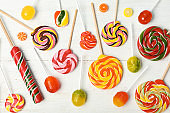 Flat lay composition with different colorful candies on white wooden background