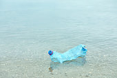Used plastic bottle floating on water surface, space for text. Recycling problem