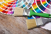 Paint brushes and color palette samples on wooden background, closeup