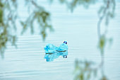Used plastic bottle floating on water surface. Recycling problem