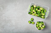 Flat lay composition with frozen brussel sprouts on light background. Vegetable preservation