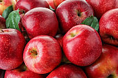 Many ripe juicy red apples as background