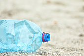 Used plastic bottle on beach, closeup with space for text. Recycling problem