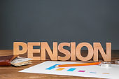 Composition with word 'PENSION' made of letters on table