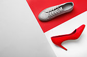 Different stylish shoes on color background, top view with space for text