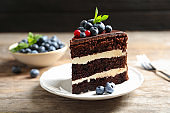 Plate with slice of chocolate sponge berry cake on wooden table