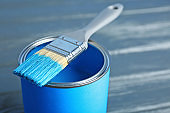 Paint can and dipped brush on wooden background, closeup