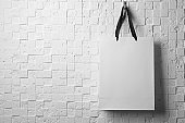 Paper shopping bag with ribbon handles hanging on white wall. Mockup for design