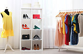 Shelving unit with shoes and purses in stylish dressing room interior