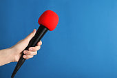 Woman holding modern microphone on color background, closeup. Space for text