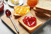 Toast bread with jams on wooden board
