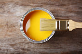 Can with yellow paint and brush on wooden background, top view