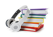 Modern headphones with hardcover books on white background