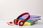 Modern headphones with hardcover books on table. Space for text