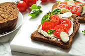 Toast bread with cherry tomatoes and mozzarella cheese on marble board, closeup