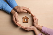 Couple holding hands near figure of house on wooden background, top view. Home insurance