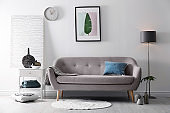 Living room interior with vases on side table and comfortable sofa near white wall
