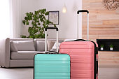 Colorful suitcases packed for journey in living room