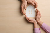 Couple holding hands near paper silhouette of house on wooden background, top view with space for text. Home insurance
