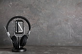 Retro microphone and headphones on table against grey background. Space for text