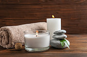 Beautiful composition with spa stones, towel and burning candles on wooden table