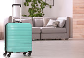 Colorful suitcase packed for journey in living room. Space for text