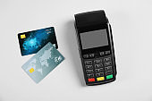 Modern payment terminal and credit cards on grey background, top view