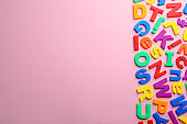 Plastic magnetic letters on color background, top view with space for text