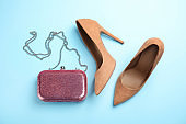 Pair of beautiful shoes and small bag on color background, flat lay