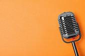 Retro microphone on color background, top view with space for text. Musical equipment