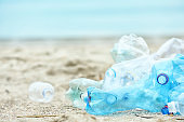 Used plastic bottles on beach, space for text. Recycling problem