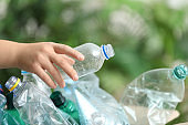 Woman putting used plastic bottle into cardboard box on blurred background, closeup. Recycling problem
