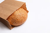 Paper bag with sesame bun on white background. Space for text