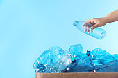 Woman putting used plastic bottle into cardboard box on color background, closeup with space for text. Recycling problem