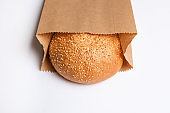 Paper bag with sesame bun on white background
