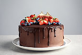 Fresh delicious homemade chocolate cake with berries on table against gray background