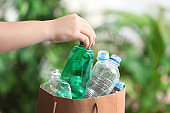 Woman putting used plastic bottle into paper bag on blurred background, closeup with space for text. Recycling problem