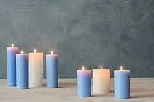 Burning candles on table against color wall with space for text