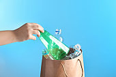 Woman putting used plastic bottle into paper bag on color background, closeup with space for text. Recycling problem