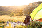 Camping gear and tourist tent in wilderness on sunny day