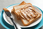 Plate with toast bread and peanut butter on table