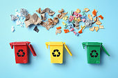 Trash bins and different garbage on color background, top view. Waste recycling concept