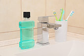 Mouthwash and holder with toothbrushes on sink in bathroom. Teeth and oral care