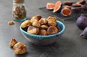 Bowl with delicious dried figs on grey table. Organic snack