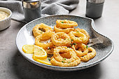 Plate with homemade crunchy fried onion rings and lemon slices on table