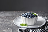 Crockery with juicy blueberries on color table