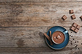 Cup of hot chocolate on wooden background, flat lay. Space for text